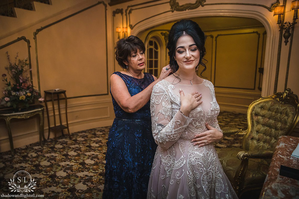 Fox Theater St. Louis wedding photo with bride getting dressed with mom