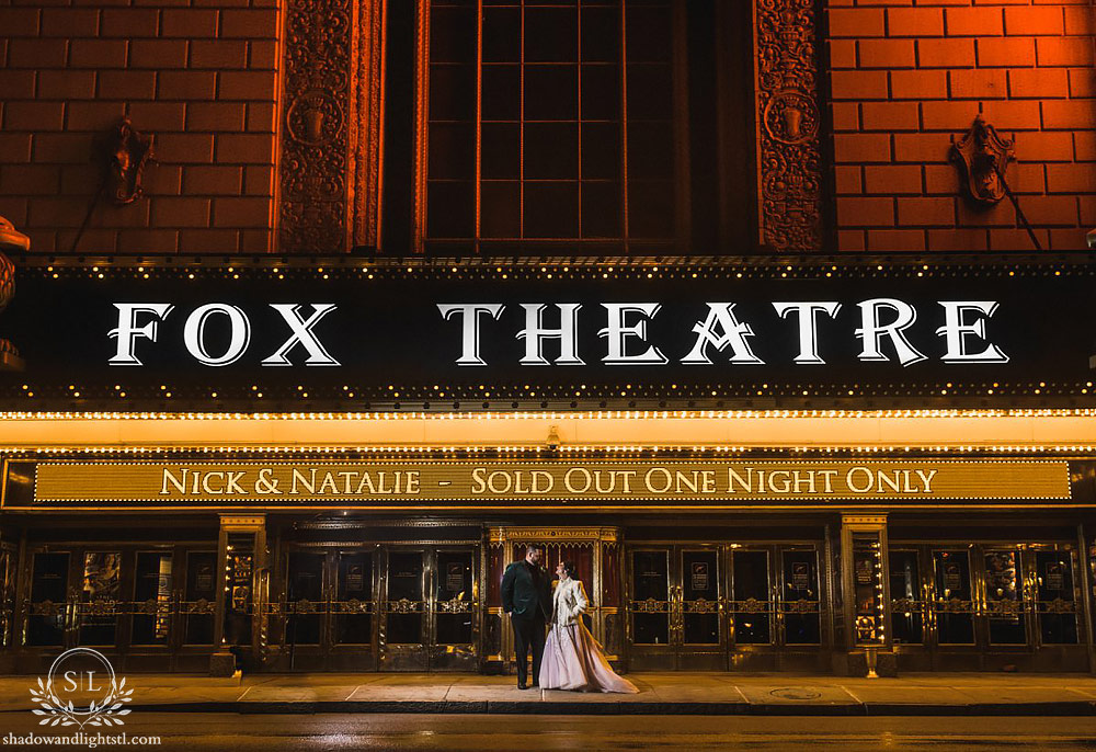 Incredible Fox Theater St. Louis wedding photo with bride and groom in front of the sign