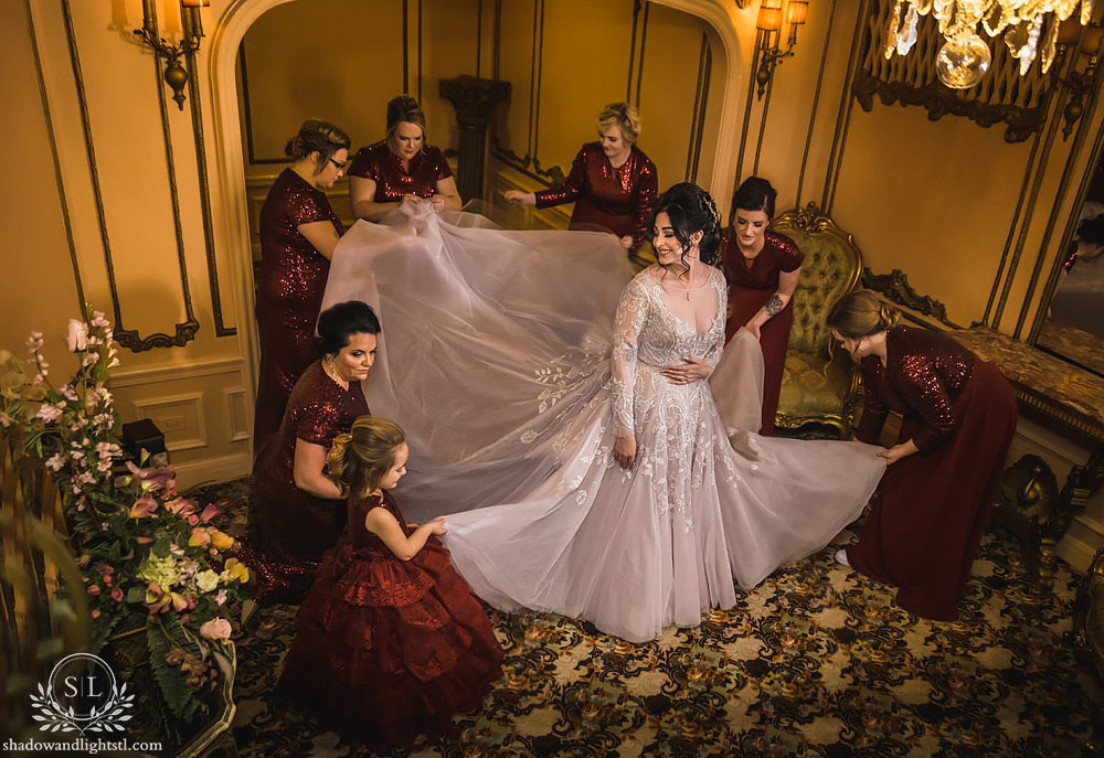 Fox Theater St. Louis wedding photo with bridesmaids fixing the bride's dress